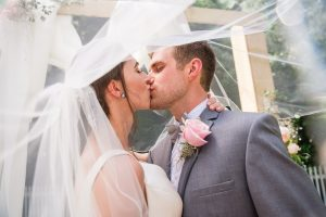 Bride and groom first kiss under vail